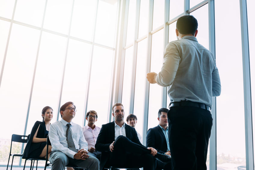 Man talking to coworkers in conference hall
