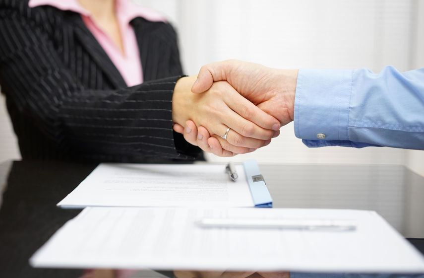 business partner and client  are handshaking over signed contrac